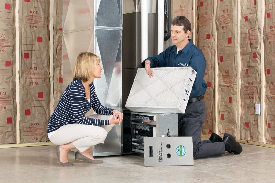 Tech in basement showing air purification filter to owner